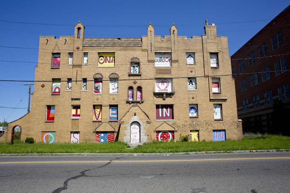 "Local artists collaborated to turn an abandoned apartment building into a massive community art project. The windows read, ""Live in Osborn."""